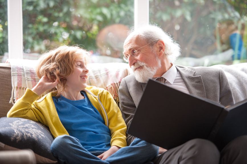 Grandfather and grandson sitting in front of window