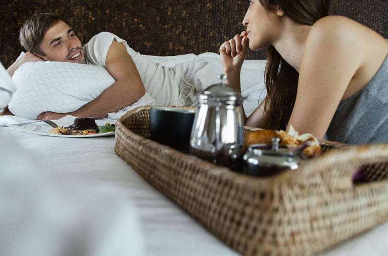 Couple having dinner in bed