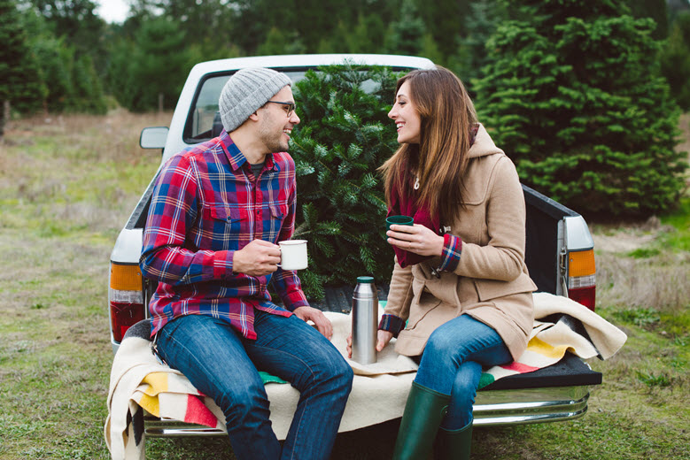 Couple sitting on back of truck