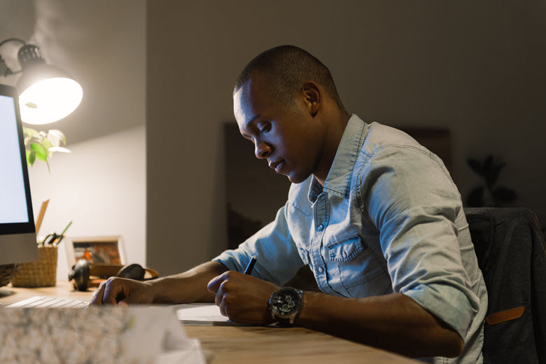 African-American man writing in home office