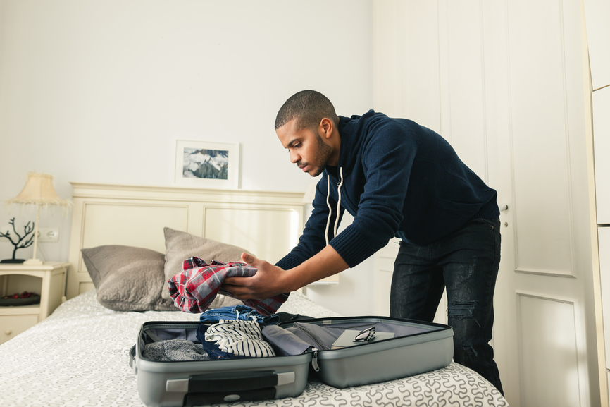 Man unpacking suitcase