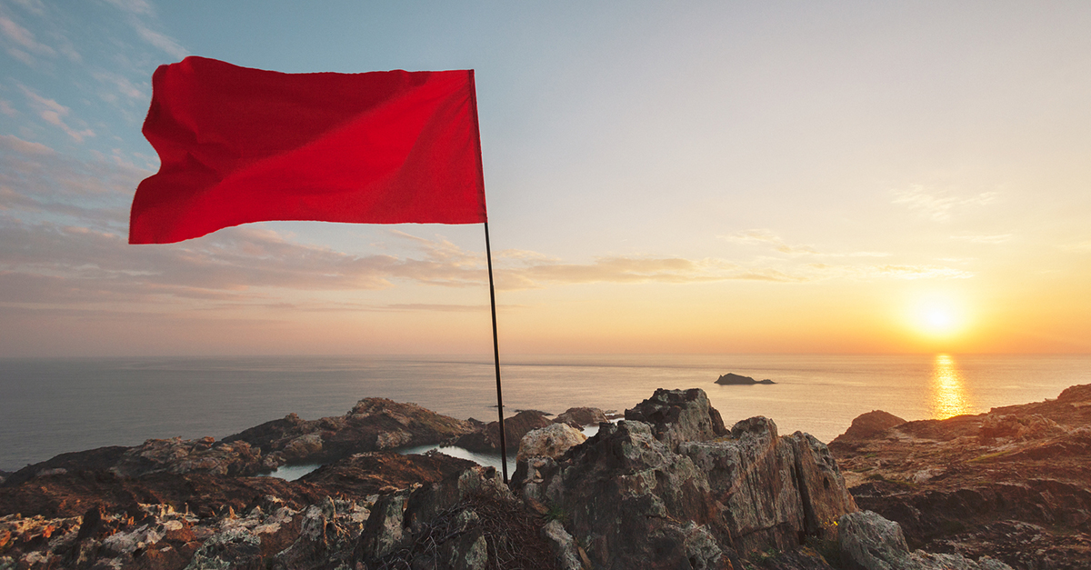 Red flag against an ocean sunset