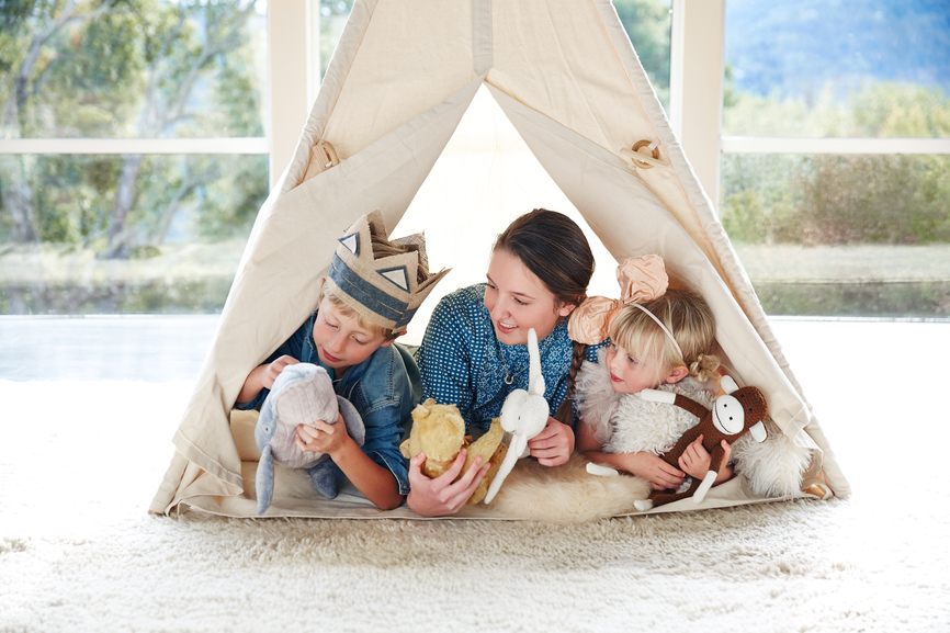 Babysitter playing in tent with kids