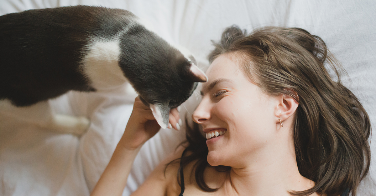 Woman playing with a kitten on the bed