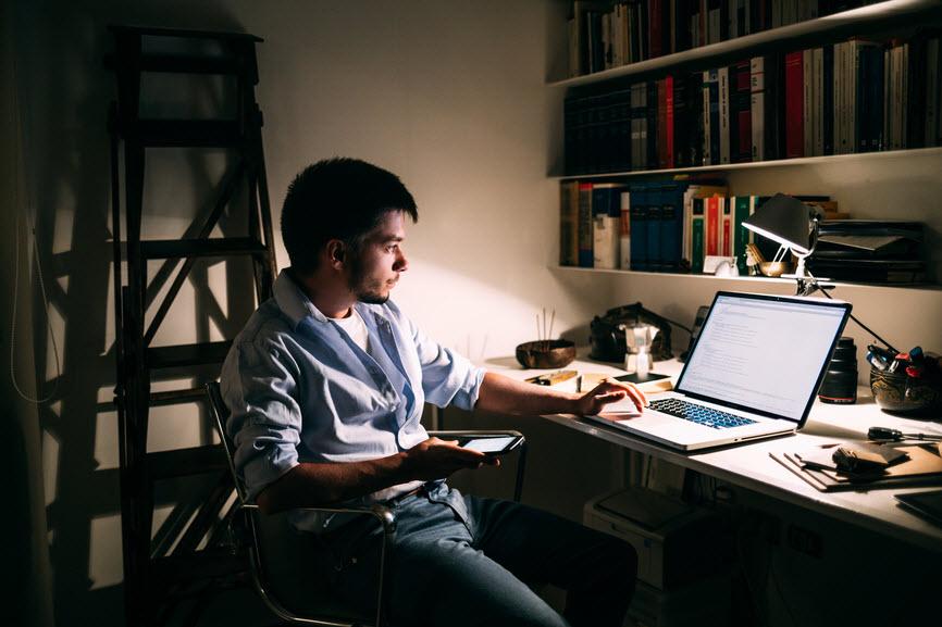 Man working on computer in a dark office