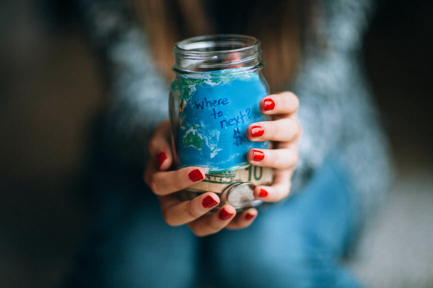 "Hands holding jar of money with the label ""where to next?"""