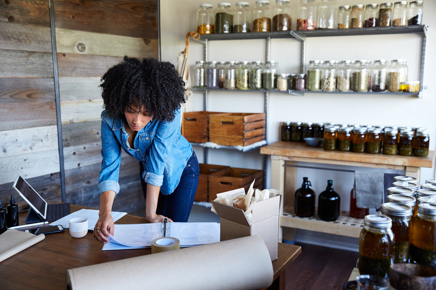 woman working at desk with paperwork and jars on shelves