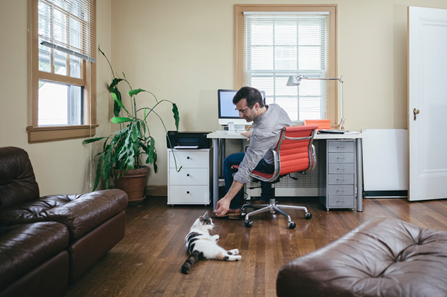 Man working in home office petting his cat